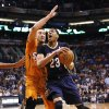 Photo - New Orleans Pelicans' Anthony Davis (23) drives past Phoenix Suns' Miles Plumlee during the first half of an NBA basketball game, Friday, Feb. 28, 2014, in Phoenix. (AP Photo/Matt York)