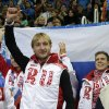Photo - Evgeny Plyushchenko of Russia, centre, gestures after receiving his results in the men's team short program figure skating competition at the Iceberg Skating Palace during the 2014 Winter Olympics, Thursday, Feb. 6, 2014, in Sochi, Russia. (AP Photo/Darron Cummings, Pool)