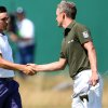 Luke Donald of England and Rickie Fowler of the US, left, shake hands at the end of their round on the first day of the British Open Golf championship at the Royal Liverpool golf club, Hoylake, England, Thursday July 17, 2014. (AP Photo/Scott Heppell)
