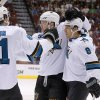Photo - San Jose Sharks' Joe Pavelski (8) celebrates his second goal in the first period of an NHL hockey game against the Phoenix Coyotes with teammates Justin Braun (61) and Matt Irwin (52) on Saturday, April 12, 2014, in Glendale, Ariz. (AP Photo/Ross D. Franklin)