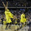 Michigan\'s Trey Burke, second from left, is lifted by Corey Person after beating Kansas 87-85 in overtime of a regional semifinal game in the NCAA college basketball tournament, Friday, March 29, 2013, in Arlington, Texas.(AP Photo/Tony Gutierrez) ORG XMIT: TXKJ160