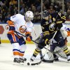 New York Islanders\' defenseman Lubomir Visnovsky (11), of the Czech Republic, battles for the puck with Buffalo Sabres\' left winger Thomas Vanek (26), of Austria, during the first period of an NHL hockey game in Buffalo, N.Y., Saturday, Feb. 23, 2013. (AP Photo/Gary Wiepert)