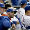 Photo - Members of the New York Mets pitching staff, including Matt Harvey, left, Dillon Gee, center, and Carlos Torres, sit in the dugout during the ninth inning of a baseball game against the Washington Nationals at Citi Field, Thursday, April 3, 2014, in New York. The Nationals defeated the Mets 8-2. (AP Photo/Seth Wenig)
