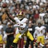 Photo - Washington Redskins quarterback Robert Griffin III (10) passes against the Oakland Raiders during the second quarter of an NFL football game in Oakland, Calif., Sunday, Sept. 29, 2013. (AP Photo/Marcio Jose Sanchez)