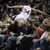 Atlanta Hawks\' Devin Harris flips over fans trying to save the ball against the Milwaukee Bucks during the first half of an NBA basketball game, Saturday, Feb. 23, 2013, in Milwaukee. (AP Photo/Jeffrey Phelps)