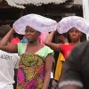 Photo - Woman from West Point, carry water on their heads as they sell water to fellow residents, in one of the areas where the Ebola virus has claimed lives  in Monrovia, Liberia, Thursday, Aug. 21, 2014. Calm returned Thursday to a slum in the Liberian capital that was sealed off in the government's attempt to halt the spread of Ebola, a day after clashes erupted between residents and security forces, but now the tens of thousands of residents worried about getting food. (AP Photo/Abbas Dulleh)
