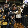 Photo - Colorado fans rush the court in celebration of a win against Kansas following an NCAA college basketball game in Boulder, Colo., Saturday, Dec. 7, 2013. Colorado won 75-72. (AP Photo/Brennan Linsley)