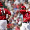 Photo - Los Angeles Angels' C.J. Wilson, right, wipes his face as he gets a visit from catcher Chris Iannetta after giving up a run to the Kansas City Royals during the first inning of a spring training baseball game Friday, March 21, 2014, in Tempe, Ariz. (AP Photo/Ross D. Franklin)