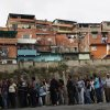 Residents wait in line at a polling station to vote in the presidential election in the Catia neighborhood of Caracas, Venezuela, Sunday, Oct. 7, 2012. President Hugo Chavez is running for re-election against opposition candidate Henrique Capriles. (AP Photo/Rodrigo Abd)