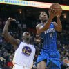 Orlando Magic forward Arron Afflalo (4) shoots in front of Golden State Warriors center Festus Ezeli (31) during the first quarter of an NBA basketball game in Oakland, Calif., Monday, Dec. 3, 2012. (AP Photo/Jeff Chiu)