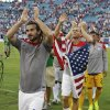 Photo - United States's Kyle Beckerman (15), Brad Davis, second from left, and other team members applaud fans as the come off the field after defeating Nigeria 2-1 in an international friendly soccer match in Jacksonville, Fla., Saturday, June 7, 2014. (AP Photo/John Raoux)