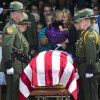 Christy Ivie, the wife of slain U.S. Border Patrol agent Nicholas Ivie, stands behind his casket after funeral services at The Church of Jesus Christ of Latter-day Saints meetinghouse in Sierra Vista, Ariz. Monday, Oct. 8, 2012. She is holding Raigan, 3. The U.S. Border Patrol agent killed in an apparent friendly fire shooting with two other agents is being remembered as a family man who loved his job and his colleagues. (AP Photo/The Arizona Republic, Michael Chow)