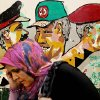 Photo -   An Egyptian woman passes a mural depicting members of the ruling Supreme Council of Armed Forces (SCAF) in Cairo, Egypt on Tuesday, May 22, 2012. On Wednesday the 23rd, Egyptians will begin two days of voting to elect a new president following more than 18 months of interim military rule. If none of the 13 contesting candidates wins a majority, a run-off will take place in June. (AP Photo/Pete Muller)