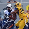 Oklahoma State receiver Tracy Moore (87) is tackled by West Virginia defender Darwin Cook (25) in the third quarter of an NCAA college football game in Morgantown, W.Va., on Saturday, Sept. 28, 2013. (AP Photo/Tyler Evert) ORG XMIT: WVTE301