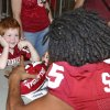 Aiden Haley, left, age four, of Oklahoma City, watches as Oklahoma defensive back Zack Sanchez, right, signs his football during Meet the Sooners Day prior to media day in Norman, Okla., Saturday, Aug. 3, 2013. (AP Photo/Sue Ogrocki) ORG XMIT: OKSO102