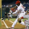 Philadelphia Phillies\' Domonic Brown, left, hits an RBI single off Washington Nationals starting pitcher Tanner Roark during the fourth inning of a baseball game, Monday, Aug. 25, 2014, in Philadelphia. At right is catcher Wilson Ramos. (AP Photo/Matt Slocum)