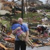 A man carries a young girl who was rescued after being trapped with her mother in their home after a tornado hit Joplin, Mo. on Sunday evening, May 22, 2011. The tornado tore a path a mile wide and four miles long destroying homes and businesses. (AP Photo/Mike Gullett) ORG XMIT: MOMG103