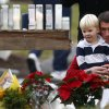 A man holds a child while paying respects to shooting victims at a makeshift memorial outside of St. Rose of Lima Roman Catholic Church, Sunday, Dec. 16, 2012, in Newtown, Conn. On Friday, a gunman killed his mother at their home and then opened fire inside the Sandy Hook Elementary School in Newtown, killing 26 people, including 20 children.(AP Photo/Julio Cortez) ORG XMIT: CTJC131