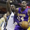 Photo - Memphis Grizzlies' Tony Allen (9) defends Los Angeles Lakers' Kobe Bryant (24) during the first half of an NBA basketball game in Memphis, Tenn., Tuesday, Dec. 17, 2013. (AP Photo/Danny Johnston)