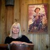 "In this Friday, Nov. 16, 2012 photo, entrepreneur Cheryl ""Happy"" Wood stands under a portrait of her grandfather Simmie Free in the Dawsonville Moonshine Distillery, in Dawsonville, Ga. Distillers are making their first batches of legal liquor in this tiny Georgia town\'s hall, not far from the mountains and the maroon, orange and gold canopy of trees that once hid bootleggers from the law. (AP Photo/David Goldman)"