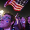 A soccer fan of the U.S. national soccer team watches a music concert minutes before of a live broadcast of the soccer World Cup match between USA and Ghana, inside the FIFA Fan Fest area on Copacabana beach, Rio de Janeiro, Brazil, Monday, June 16, 2014. (AP Photo/Leo Correa)