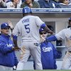 Photo - Los Angeles Dodgers manager Don Mattingly, left, and Carl Crawford, right, congratulate Juan Uribe after he scored against the San Diego Padres in the fourth inning of baseball game Tuesday, April 1, 2014, in San Diego.  (AP Photo/Lenny Ignelzi)