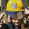 Students from Good Shepherd Lutheran School reach for a firefighter\'s helmet as students are given the opportunity to wear it after being shown the equipment on a fire truck Wednesday afternoon, Oct. 8, 2008. Midwest City firefighters are conducting fire safety training for elementary school students as part of the department\'s Fire Prevention Month activities. BY JIM BECKEL, THE OKLAHOMAN