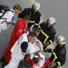 Photo - Rescue workers transport a victim from a train that derailed,  in Bretigny sur Orge, south of Paris, Friday July, 12, 2013. A packed passenger train skidded off its rails after leaving Paris on Friday, leaving seven people believed dead and dozens injured as train cars slammed into each other and overturned, authorities said. (AP Photo/Jacques Brinon)