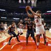 Chicago Bulls center Joakim Noah (13) shoots a reverse layup past Atlanta Hawks\' Kyle Korver (26) and Josh Smith (5) during the first half of an NBA basketball game Monday, Jan. 14, 2013, in Chicago. (AP Photo/Charles Rex Arbogast)