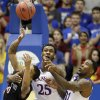 Photo - Kansas' Tarik Black (25) and Jamari Traylor (31) battle San Diego State's Aqeel Quinn for a rebound during the first half of an NCAA college basketball game Sunday, Jan. 5, 2014, in Lawrence, Kan. (AP Photo/Charlie Riedel)