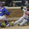 Photo - New York Mets catcher Travis d'Arnaud (15) tags out Atlanta Braves' Justin Upton during the eighth inning of a baseball game on Friday, April 18, 2014, in New York. (AP Photo/Frank Franklin II)
