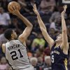 Photo - San Antonio Spurs forward Tim Duncan, left, shoots against New Orleans Pelicans center Jeff Withey during the first half of an NBA basketball game on Saturday, March 29, 2014, in San Antonio. (AP Photo/Darren Abate)