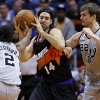San Antonio Spurs\' Kawhi Leonard (2) and Tiago Splitter (22), of Brazil, pressure Phoenix Suns\' Luis Scola (14), of Argentina, during the first half of an NBA basketball game, Sunday, Feb. 24, 2013, in Phoenix. (AP Photo/Matt York)