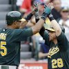 Oakland Athletics\' Chris Young, left, and Eric Sogard celebrate as both score on Sogard\'s home run against the Los Angeles Angels in the third inning of a baseball game in Anaheim, Calif., Sunday, July 21, 2013. (AP Photo/Reed Saxon)