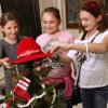 From left, Asher Elementary School fourth and fifth grade students Victoria Frankovich, Madilynn Larman and Malorie Larman place a red cowboy hat atop their school\'s decorated tree. The theme of their tree is \'A Cowboy Western Christmas.\' School children from across the state came to the state Capitol to decorate 36 small Christmas trees in the hallways and rotunda. Gov. Mary Fallin and State Superintendent Janet Barresi joined Santa Claus in greeting the students at each tree after they were decorated. Many of the children stayed to watch the governor light the state Christmas tree on the south plaza on Thursday, Nov. 29, 2012. Photo by Jim Beckel, The Oklahoman