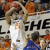 Oklahoma State \'s Markel Brown (22) puts up a shot over Kansas\' Travis Releford (24) during the college basketball game between the Oklahoma State University Cowboys (OSU) and the University of Kanas Jayhawks (KU) at Gallagher-Iba Arena on Wednesday, Feb. 20, 2013, in Stillwater, Okla. Photo by Chris Landsberger, The Oklahoman