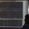 A woman looks at displays of the Stock Exchange in Athens Tuesday, Oct. 30, 2012. Shares recovered slightly from heavy losses Monday, amid continued uncertainty over a new austerity package due to divisions in the country\'s coalition government. Conservative Prime Minister Antonis Samaras said Tuesday that the government had essentially ended negotiations on new austerity measures and warned of