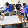 Oklahoma City Thunder\'s Russell Westbrook looks at a map with rescue workers at a command center in Moore, Wednesday May 22, 2013. Members of the Oklahoma City Thunder and family members took a tour of the area hit by a tornado on Monday afternoon. Photo By Steve Gooch, The Oklahoman