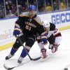 New York Islanders\' Frans Nielsen, left, and New Jersey Devils\' David Clarkson battle for the puck during the first period of the NHL hockey game on Sunday, Feb. 3, 2013, in Uniondale, N.Y. (AP Photo/Seth Wenig)