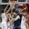 Oklahoma\'s Je\'lon Hornbeak (5), Romero Osby (24) and Amath M\'Baye (22) defend on West Virginia \'s Deniz Kilicli (13) during the first half of the college basketball game between the University of Oklahoma Sooners (OU) and the West Virginia University Mountaineers (WVU) at the Lloyd Noble Center on Wednesday, March 6, 2013, in Norman, Okla. Photo by Chris Landsberger, The Oklahoman