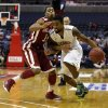 George Mason guard Sherrod Wright (10) tries to get past Oklahoma guard Isaiah Cousins (11) during the second half of an NCAA college basketball game in the BB&T Classic, Sunday, Dec. 8, 2013, in Washington. Oklahoma won 81-66. (AP Photo/Alex Brandon)