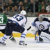 Photo - Winnipeg Jets goalie Ondrej Pavelec (31), of Czech Republic, blocks a shot from Dallas Stars left wing Ray Whitney (13) as the Jets' Dustin Byfuglien (33) assists on the pressure in the first period of an NHL hockey game, Saturday, Oct. 26, 2013, in Dallas. (AP Photo/Tony Gutierrez)