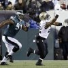 Photo - New Orleans Saints' Mark Ingram, right, cannot pull in a pass as Philadelphia Eagles' Fletcher Cox (91) pursues during the first half of an NFL wild-card playoff football game, Saturday, Jan. 4, 2014, in Philadelphia. (AP Photo/Julio Cortez)