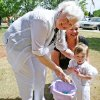 Touchmark resident Mary Koop helps her granddaughter Rose Estella Yarbrough with her basket as daughter Marilyn Koop Grammer takes in the fun at the annual Easter egg hunt, co-sponsored by Touchmark at Coffee Creek and the Coffee Creek Homeowners Associat