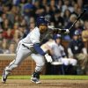 Photo - Milwaukee Brewers' Carlos Gomez singles in Jean Segura to score a run against the Chicago Cubs during the ninth inning of a baseball game, Monday, July 29, 2013, in Chicago. (AP Photo/Jim Prisching)