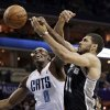 Charlotte Bobcats\' Bismack Biyombo (0) and San Antonio Spurs\' Jeff Ayres (11) battle for a rebound during the first half of an NBA basketball game in Charlotte, N.C., Saturday, Feb. 8, 2014. (AP Photo/Chuck Burton)