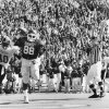 11/3/84. UNIVERSITY OF OKLAHOMA / COLLEGE FOOTBALL / TOUCHDOWN: OU\'s Keith Jackson ends a 58-yard TD pass play as the crowd cheers and the Ruf-Neks fire their shotguns (right) in a game against Missouri won by the Sooners 49-7 in Norman. Staff photo by Doug Hoke taken 11/3/84.