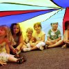 Children sitting under a parachute during