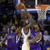 Photo - Sacramento Kings' DeMarcus Cousins, right, blocks a shot by Golden State Warriors' Harrison Barnes, center, with help from John Salmons (5) during the first half of an NBA preseason basketball game Monday, Oct. 7, 2013, in Oakland, Calif. (AP Photo/Marcio Jose Sanchez)
