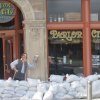 Photo - FILE - In this May 31, 2013, file photo, sandbags are piled around the Parlor City Pub and Eatery in Cedar Rapids, Iowa, where workers placed a cardboard cutout of a man drinking beer. Congress sent the White House a $12.3 billion water projects bill half the size of its last one seven years ago — before the economy sank into a deep recession that helped swell the government's debt and before lawmakers swore off cherry-picking pet projects for folks back home.  (AP Photo/Ryan J. Foley, File)